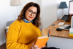 curvy latin woman sitting reading a book at her home office