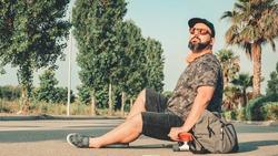 Curvy man in shorts sitting on a skateboard smiling.