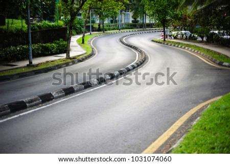 Curvy road with divider at outskirt residence area. Residents walk along path beside the main road. #1031074060