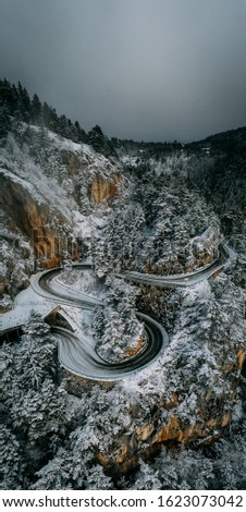 Curvy windy mountain road in snow covered forest, top down aerial view. Winter landscape.