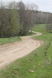 Curvy zigzag gravel road through the trees and bushes on one side and green meadow on the other in Lithuania