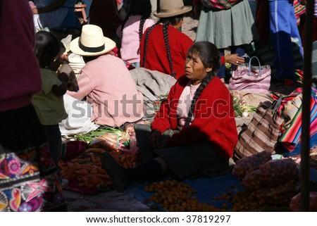 CUSCO, PERU - AUGUST 24 : Quechua Indian woman sells vegetables in the Pisac Market August 24, 2008 in Cusco, Peru. - stock photo