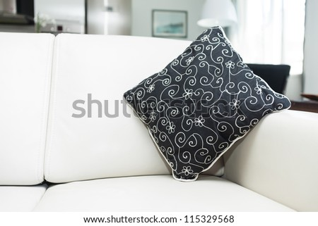 Cushion on modern leather sofa in cozy home