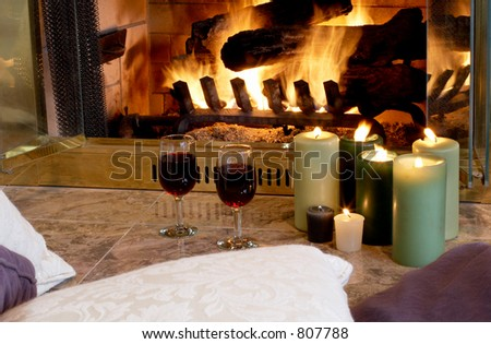 Cushions & candles by the fire - stock photo