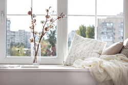 cushions and a knitted plaid on the windowsill. A cozy window sill.