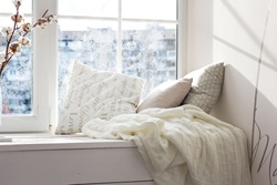 cushions and a knitted plaid on the windowsill. A cozy winter window sill.