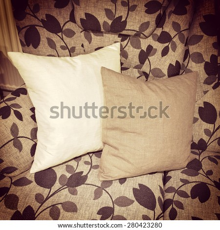 Cushions decorating a sofa with floral design, retro style furniture.