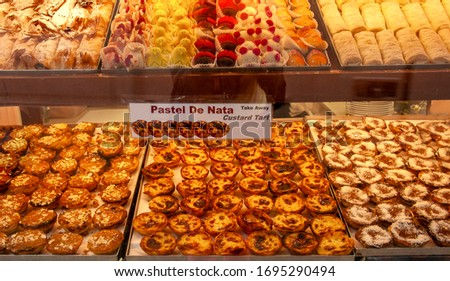 Custard tart, traditional Portuguese dessert. Pastel de nata o egg tart and typical Portuguese pastries on the a shop window. Colorful background from traditional pastries.  Foto stock ©