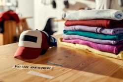 Custom apparel, clothes neatly folded on shelves. Stack of colorful clothing and baseball cap in the store. Horizontal shot. Selective focus