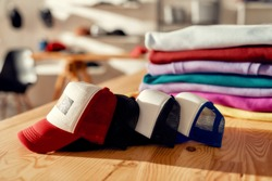 Custom apparel, clothes neatly folded on shelves. Stack of colorful clothing and baseball caps in the store. Horizontal shot. Selective focus