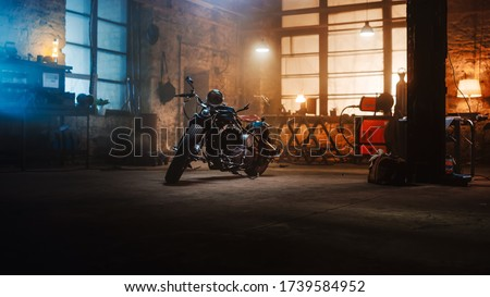 Custom Bobber Motorbike Standing in an Authentic Creative Workshop. Vintage Style Motorcycle Under Warm Lamp Light in a Garage. Foto stock ©
