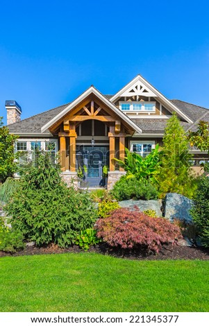 Custom built luxury house entrance with nicely trimmed and landscaped front yard in Canada.