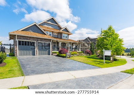 Custom built luxury house for sale with nicely trimmed and designed front yard, lawn in a residential neighborhood in Canada. For sale sign in front of the house by real estate agency.