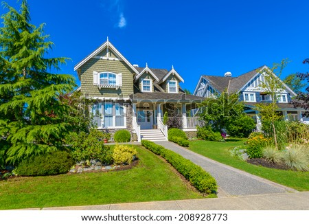 Custom built luxury house with nicely paved doorway and trimmed front yard, lawn in a residential neighborhood. Vancouver Canada.