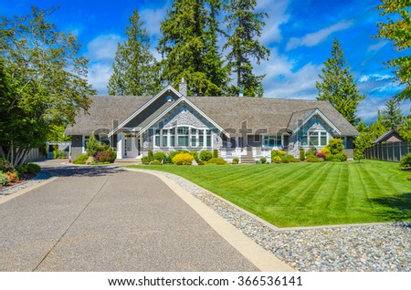 Custom built luxury house with nicely trimmed and landscaped front yard, lawn and driveway in a residential neighborhood. Vancouver Canada. #366536141