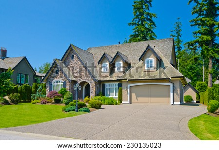 Custom built luxury house with nicely trimmed and landscaped front yard lawn and driveway to garage in a residential neighborhood. Vancouver Canada. #230135023