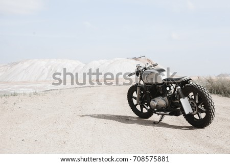 Custom cafe racer motorcycle parking on the road right side and sunset, sea background, nobody