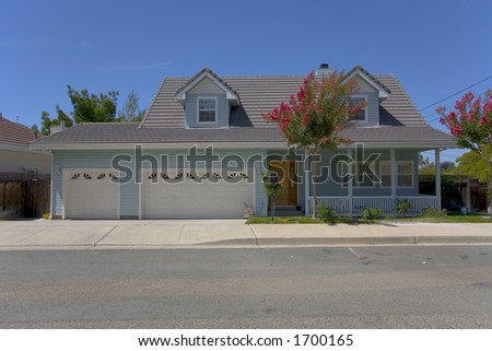 Custom home featuring two dormer windows and a covered porch.