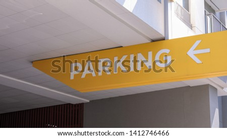 Custom parking sign with white letters and an arrow pointing to the left under a ceiling of a parking garage