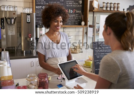 Customer at counter of coffee shop pays using touch screen