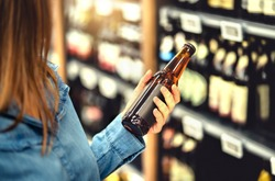 Customer buying beer in liquor store. Lager, craft or wheat beer. IPA or pale ale. Woman at alcohol shelf. Drink section and aisle in supermarket. Lady holding bottle in hand. Drink business concept.