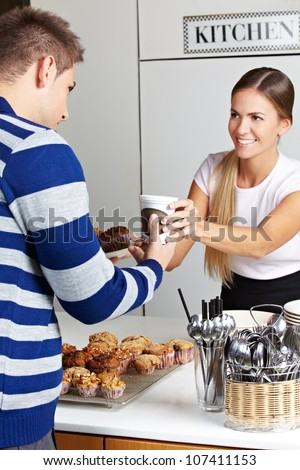 Customer buying coffee and muffins in caf�© from smiling woman