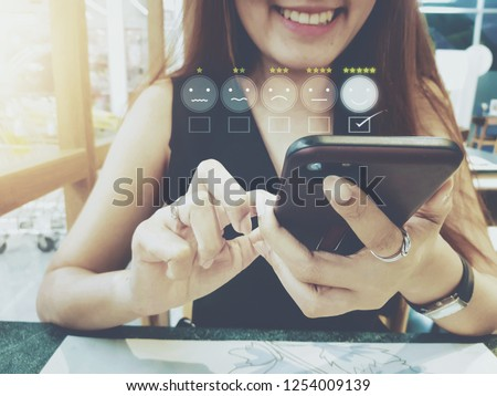 Customer experience concept, happy business women holding the smartphone with a checked box on excellent smiley face and rating for a satisfaction survey. stock photos