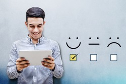 Customer Experience Concept, Happy Businessman holding digital Tablet with a checked box on Excellent Smiley Face Rating for a Satisfaction Survey