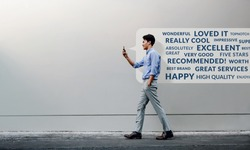 Customer Experience Concept. Reading Positive Online Review via Smartphone. Smiling Young Businessman Using Mobile Phone while Walking by the Urban Building Wall. Side View. Full Length