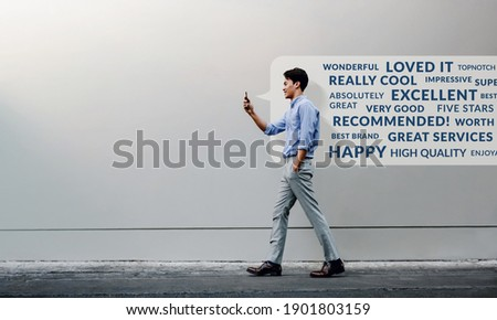 Customer Experience Concept. Reading Positive Online Review via Smartphone. Smiling Young Businessman Using Mobile Phone while Walking by the Urban Building Wall. Side View. Full Length ストックフォト ©