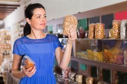 Customer female is choosing sweet dry fruits in organic shop.