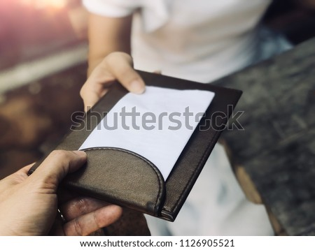 Customer get bill and receipt from waiter in restaurant. Black leather tray with receipt bill. Service and restaurant catering concept. Copy space, selective focus