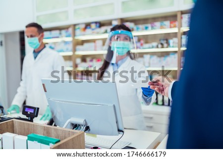 Customer giving prescription for medication to a pharmacist.