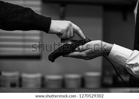 Customer hand paying with credit card. Credit card payment and electronic bank concept. Cashier holds credit card reader in cafe on defocused background. Credit card terminal for cashless payments.