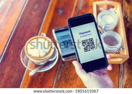 Customer hand using smart phone to scan QR code tag on another smart with coffee in coffee shop or restaurant to accepted generate digital pay without money. Qr code payment concept.