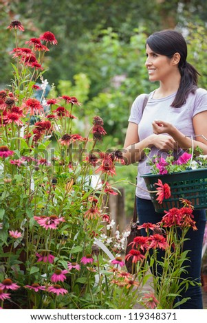 Customer holding a basket while smiling in garden center