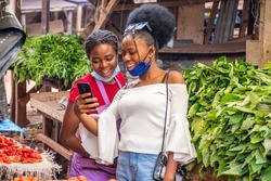 customer in a market showing a trader something exciting on her phone