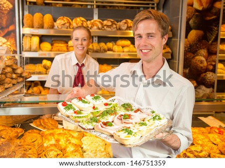 Customer in bakery with tablet full of sandwiches