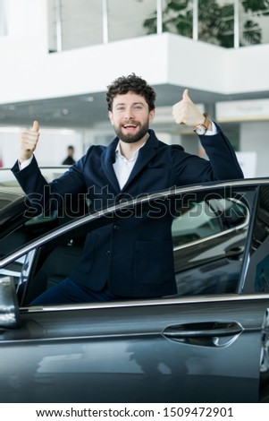 Customer in car dealership. Young man knelt down with keys in hand.