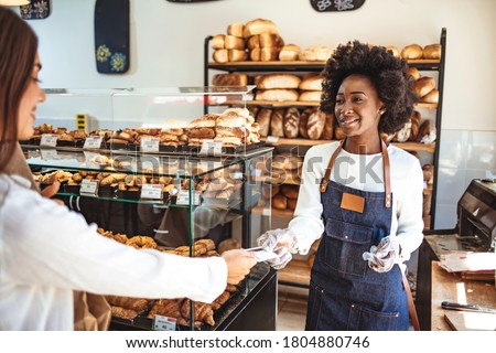 Customer making a credit card payment in a bakery. Paying with credit card for a baguette. Paying by credit card in the store with bakery products. Paying with a credit card in the bakery