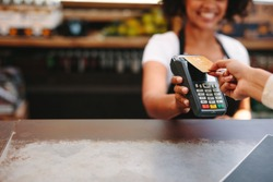 Customer making wireless or contactless payment using credit card. Smiling cashier accepting payment over nfc technology.