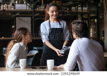 Customer, man paying by contactless credit card with NFC technology in cafe, attractive smiling waitress holding card reader machine, young couple on date in cozy restaurant or coffeehouse