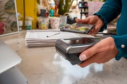 Customer paying bill through smartphone using NFC technology. Closeup of hand making payment through contactless machine. Woman hand holding mobile phone