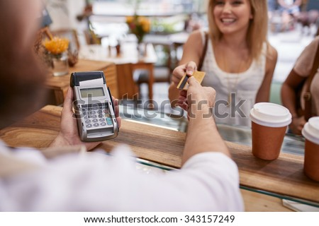 Customer paying for their order with a credit card in a cafe. Bartender holding a credit card reader machine and returning the debit card to female customer after payments. #343157249