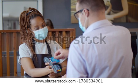 Customer paying with credit card for buying food on counter in modern cafe wearing safety mask. African waitress holding card reader for client to pay for order in coffee shop.