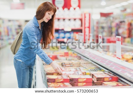 Customer picking a product in the frozen aisle of a supermarket #573200653