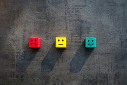 Customer satisfaction measurement unhappy okay and happy faces on coloured red yellow green wood blocks - Commercial business success client rating metrics scale - Excellence, KPI and feedback concept