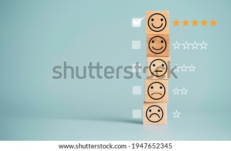 Customer satisfaction survey concept, human face icons print screen on wooden cube block with stars and mark on blue background for evaluate product and service. Foto stock ©