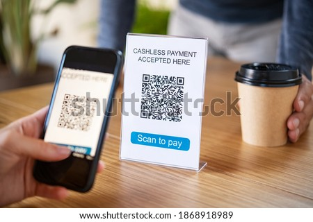Customer scanning tag in coffee shop to pay online. Close up of hand scanning qr code for cashless payment at cafeteria. Girl framing qr code to make a purchase, small business accepts digital payment