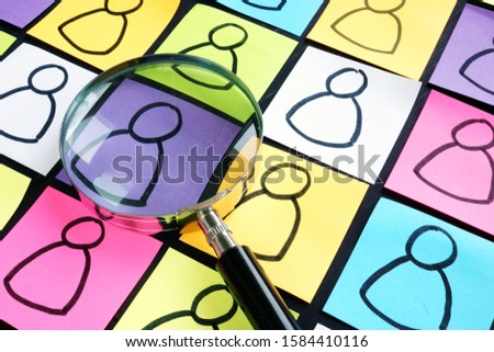 Customer Segmentation concept. Multicolored sheets with figures and magnifying glass